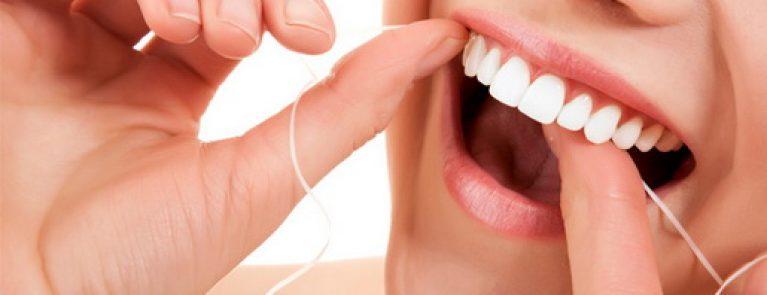 Pessoa fazendo usando fio dental | Quando devo fazer limpeza nos dentes?
