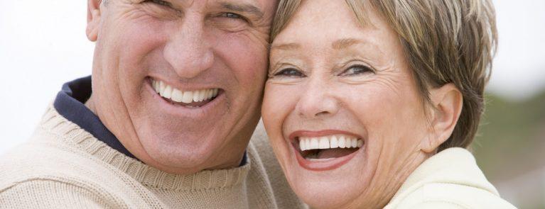 Casal de idosos sorrindo | Implante dentário: o que é e quais são os benefícios?