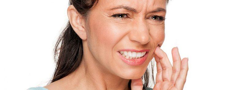 Mulher com dor de dente | O que é doença periodontal?