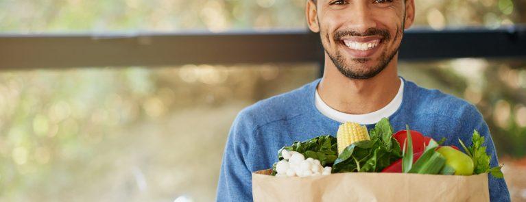 homem negro sorrindo segurando sacola de papel com frutas e legumes dentro   Como a alimentação pode influenciar na saúde bucal?