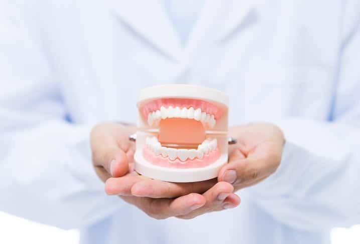 Pessoa segurando prótese dentária   Prótese dentária fixa x móvel