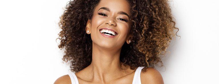 Mulher negra sorrindo dentes brancos | Tudo sobre lente de contato dental