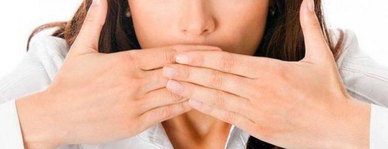 Mulher escondendo a boca | Mitos e verdades sobre o mau hálito