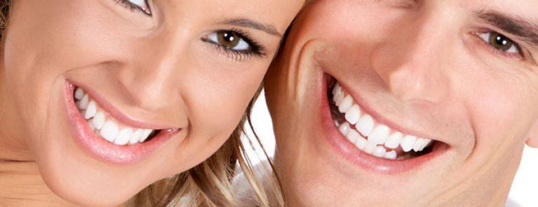 Casal sorrindo | Qual a diferença entre o clareamento dentário no consultório e o caseiro?