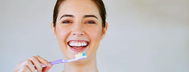Como escovar os dentes corretamente | Mulher sorrindo escovando os dentes | Clínica Vittal