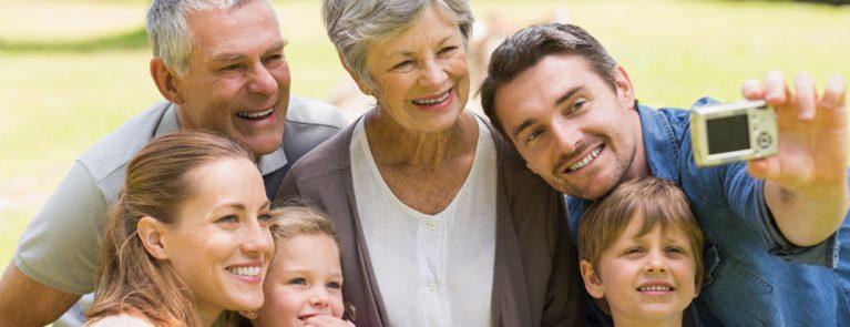 Avó, avô, pai, mãe, menino e menina tirando foto | Doenças odontológicas que podem aparecer em cada idade