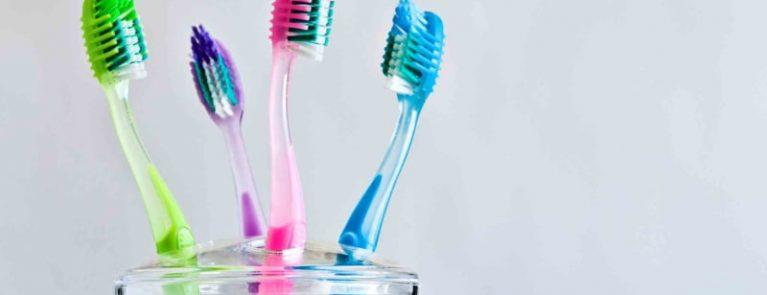 Escovas de dente coloridas dentro do pote | Tipos de escovas de dente