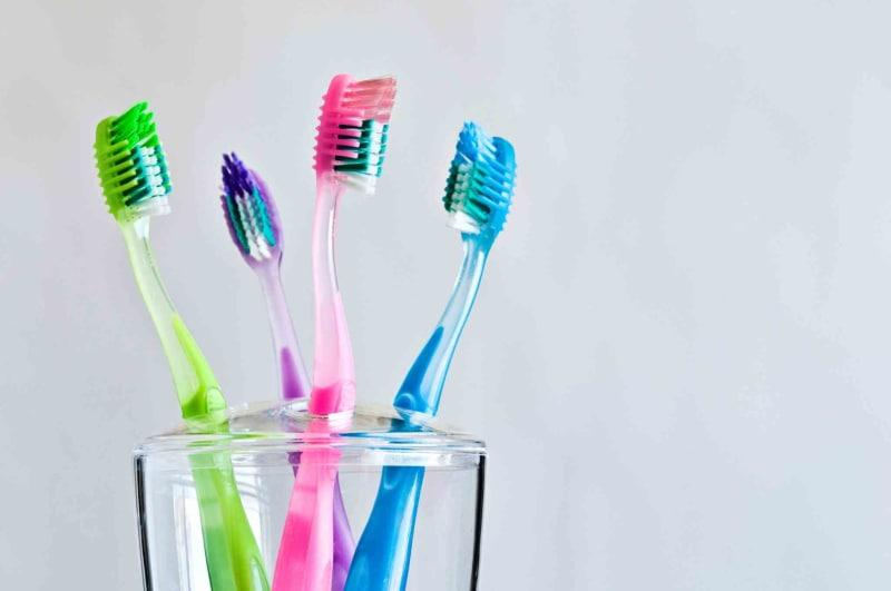 Escovas de dente coloridas dentro do pote   Tipos de escovas de dente