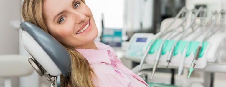 Mulher sorrindo em consultório odontológico | O que você precisa saber sobre a reabilitação oral